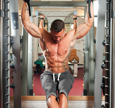 six persons: Portrait of a strong fit young man exercising in a gym.