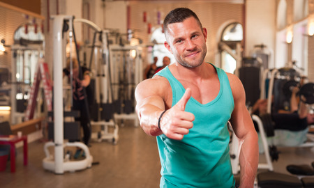 man thumbs up: Portrait of a strong fit young man exercising in a gym.