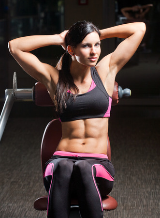 six pack abs: Portrait of a slender super fit young brunette woman. Stock Photo