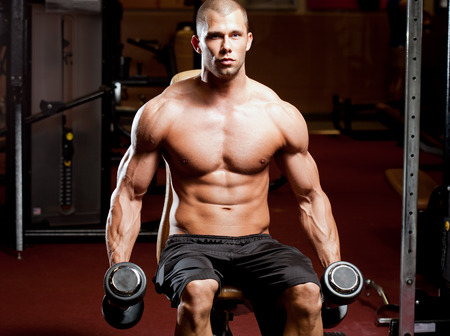 man working out: Portrait of a muscular strong young man working out.