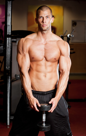 upper half: Portrait of a muscular strong young man working out.