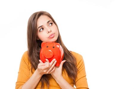 Portrait of a beautiful young brunette woman holding orange piggy bank. Stock Photo - 29112353