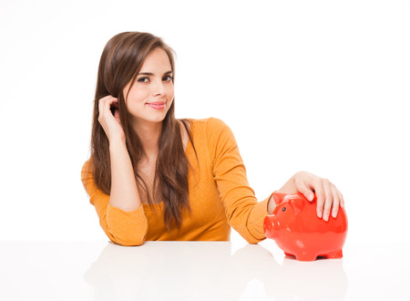 Portrait of a beautiful young brunette woman holding orange piggy bank. Stock Photo - 29112364