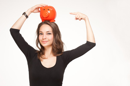 Portrait of a gorgeous young brunette woman posing with colorful piggy bank  photo