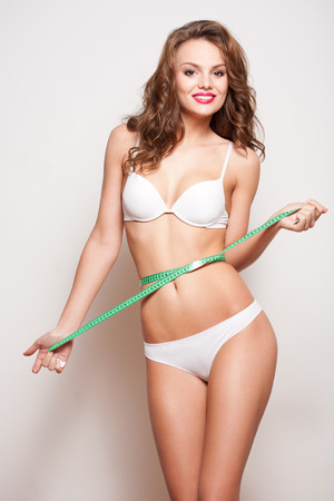 woman panties: Portrait of a young slender brunette wearing white lingerie