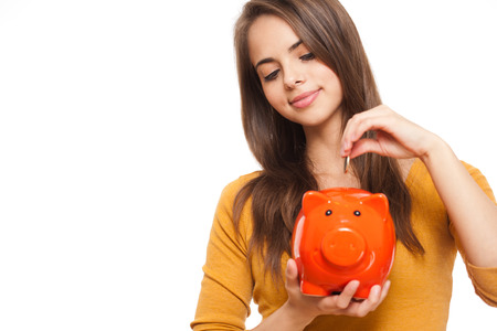 young add: Portrait of an attractive young brunette with piggy bank.