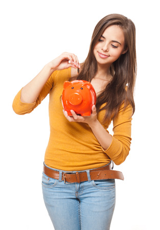 Portrait of a beautiful young brunette posing with colorful piggy bank. photo