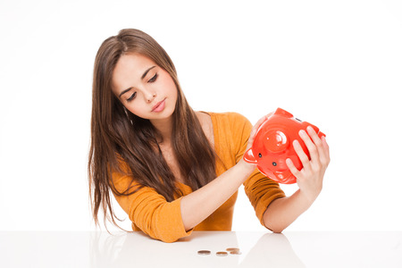 disappointed: Portrait of an attractive young brunette with piggy bank.