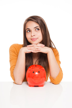 Portrait of an attractive young brunette with piggy bank. photo