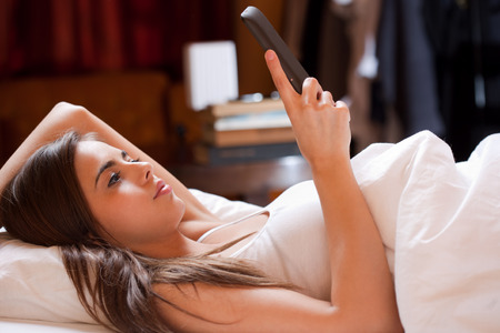 Cute young brunette  using tablet computer laying in bed. photo