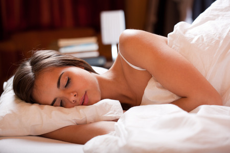 white bed: Beautiful young brunette woman laying in bed going to sleep.