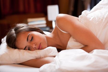 gente durmiendo: Joven y bella mujer morena en la cama por el que se va a dormir. Foto de archivo