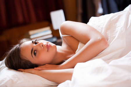 woman sleep: Beautiful young brunette woman laying in bed going to sleep.
