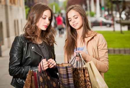 Couple of beautiful young brunette women with shopping bags outdoors. photo