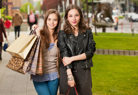 Fashionable shopping beauties outdoors in the city. photo
