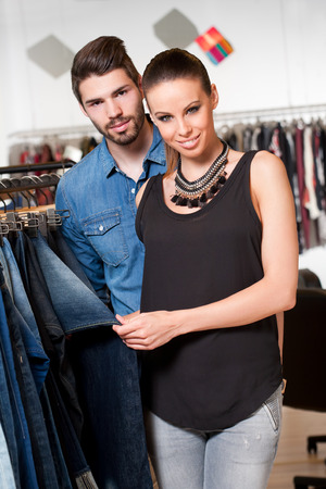 Portrait of attractive young couple shopping for clothes. photo