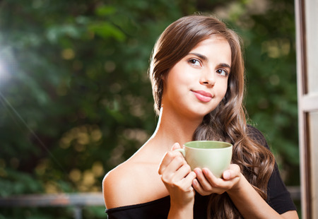 woman drinking tea: Portrait of a gorgeous cool young brunette woman holding green cup. Stock Photo