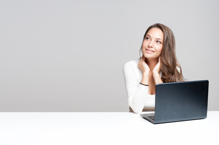 Attractive young brunette woman using her laptop.