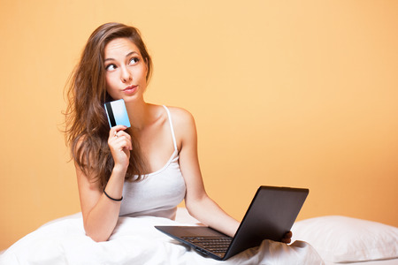 mujer pensativa: Retrato de una hermosa morena joven usando la computadora portátil.