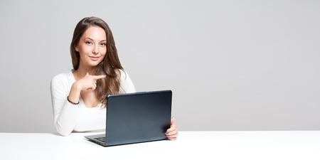 belle brune: Portrait d'une jeune brunette magnifique utilisant un ordinateur portable.