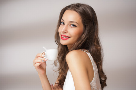 Beautiful fashionable young brunette with a cup of coffee.