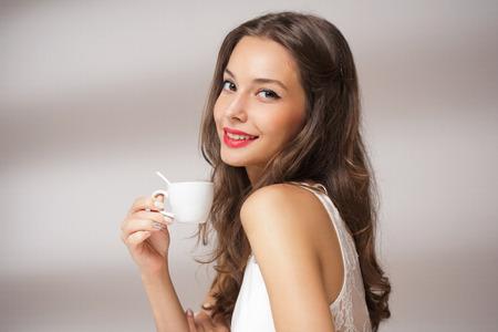 Schöne moderne junge Brünette mit einer Tasse Kaffee. Standard-Bild - 33022596