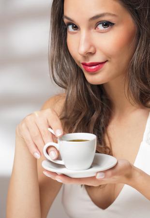 mujer tomando cafe: Joven y bella morena de moda con una taza de café.