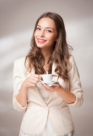 gorgeous businesswoman: Beautiful fashionable young brunette with a cup of coffee.