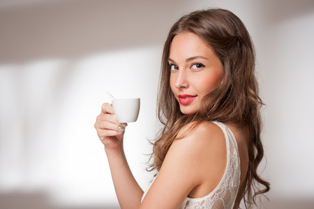 Portrait of gorgeous young brunette woman holding cup of coffee.
