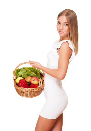 Fit gorgeous young blond woman holding wicker basket full of fresh vegetables. photo
