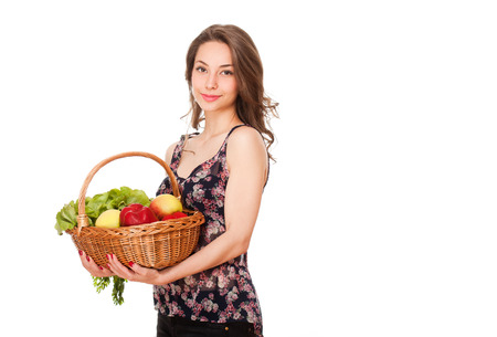 Brunette beauty holding a basket full of fresh vegetables and fruits. photo