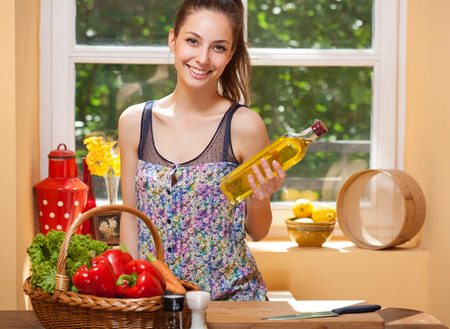 cooking oil: Fit brunette beauty preparing healthy food in the kitchen. Stock Photo