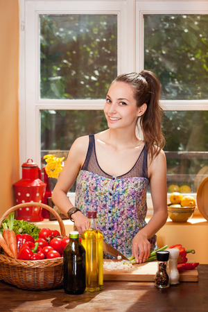 Beautiful young brunette woman preparing healthy food in the kitchen. Reklamní fotografie