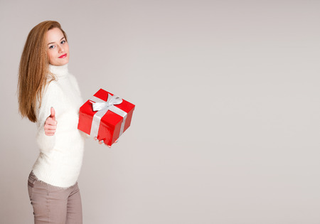 Portrait of a gorgeous young woman holding bright red gift box. photo