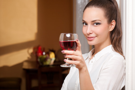 Portrait of a beautiful young brunette woman holding a glass of fine wine.
