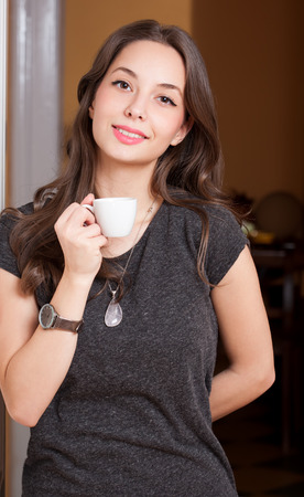 sexy asian girl: Portrait of a gorgeous young brunette woman holding cup of coffee.