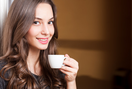 Closeup portrait of a gorgeous young brunette woman holding cup of coffee. Archivio Fotografico