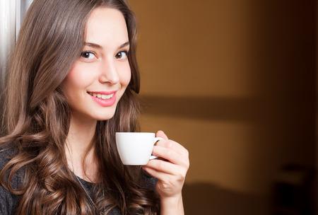 Detailansicht-Porträt einer wunderschönen jungen Frau, brünett mit Tasse Kaffee. Standard-Bild - 35379249