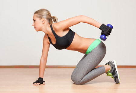 mujer arrodillada: Retrato de una joven hermosa mujer rubia de fitness.