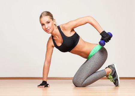 mujer arrodillada: Retrato de una hermosa niña rubia de fitness magra.