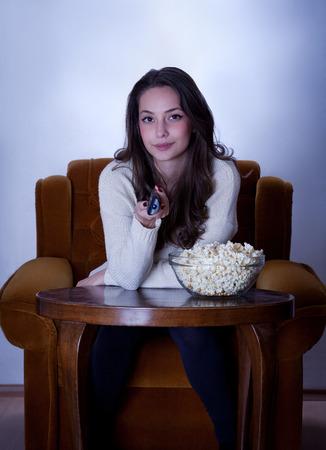 woman watching tv: Beautiful young brunette woman watching TV in armchair. Stock Photo