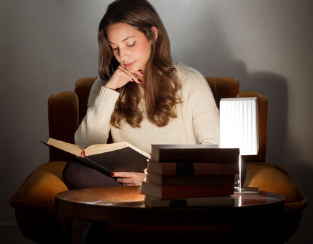 student reading: Portrait of brunette beauty reading books at home.