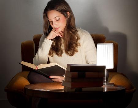 Portret van de brunette schoonheid lezen van boeken thuis. Stockfoto