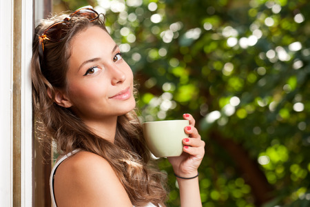 Smiling brunette beauty holding green cup with hot beverage. Stockfoto