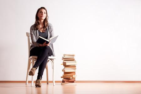 Porträt eines jungen brunette Student mit einem großen Stapel der Bücher.