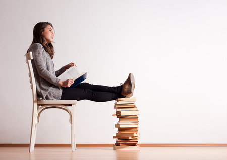 Portrait of a young brunette student with a large pile of books. photo