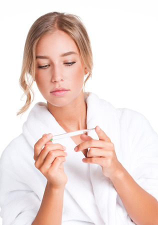 body temperature: Portrait of a worried young blond beauty checking her temperature. Stock Photo