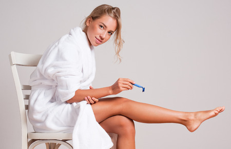 Portrait of a beautiful young blond shaving her legs. Stock Photo