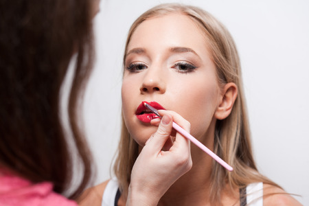 tanned girl: Makeup artist working on a young blond beauty. Stock Photo