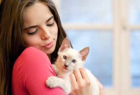 smiling cat: Portrait of a beautiful brunette holding a cute kitten. Stock Photo